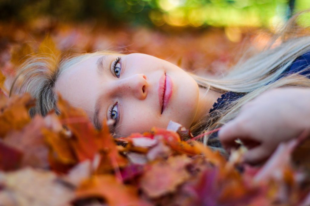 Woman lying on fall leaves
