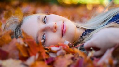 Woman lying on fall leaves