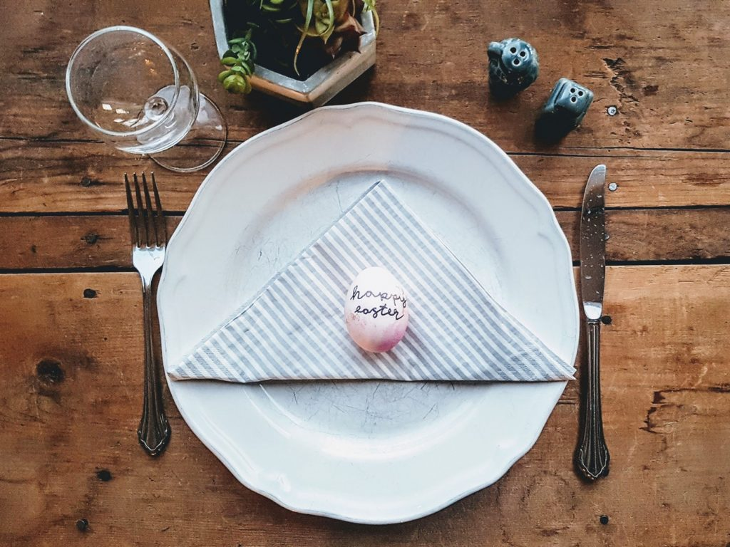 Easter egg on white plate with fork and knife on wooden table