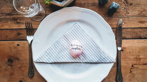 Easter egg on a white plate with fork and knife on a wooden table