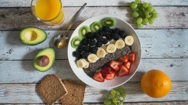 Health breakfast bowl with toast, avocado, and orange juice